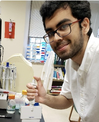a young man with dark hair and a beard wearing glasses in a lab