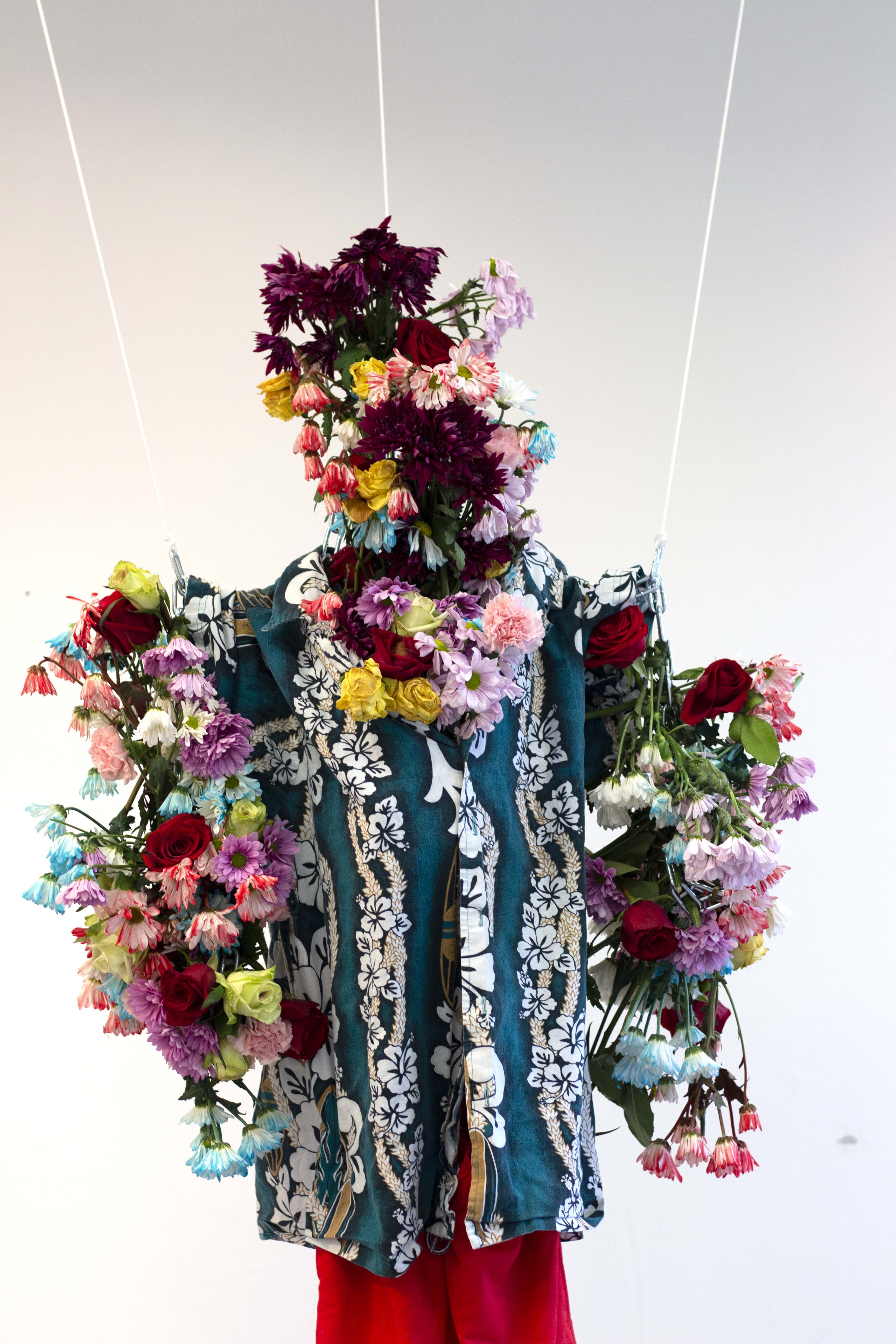 A sculpture made of flowers and clothing.