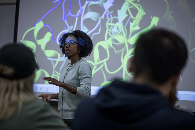 an African American woman teaches at a whiteboard