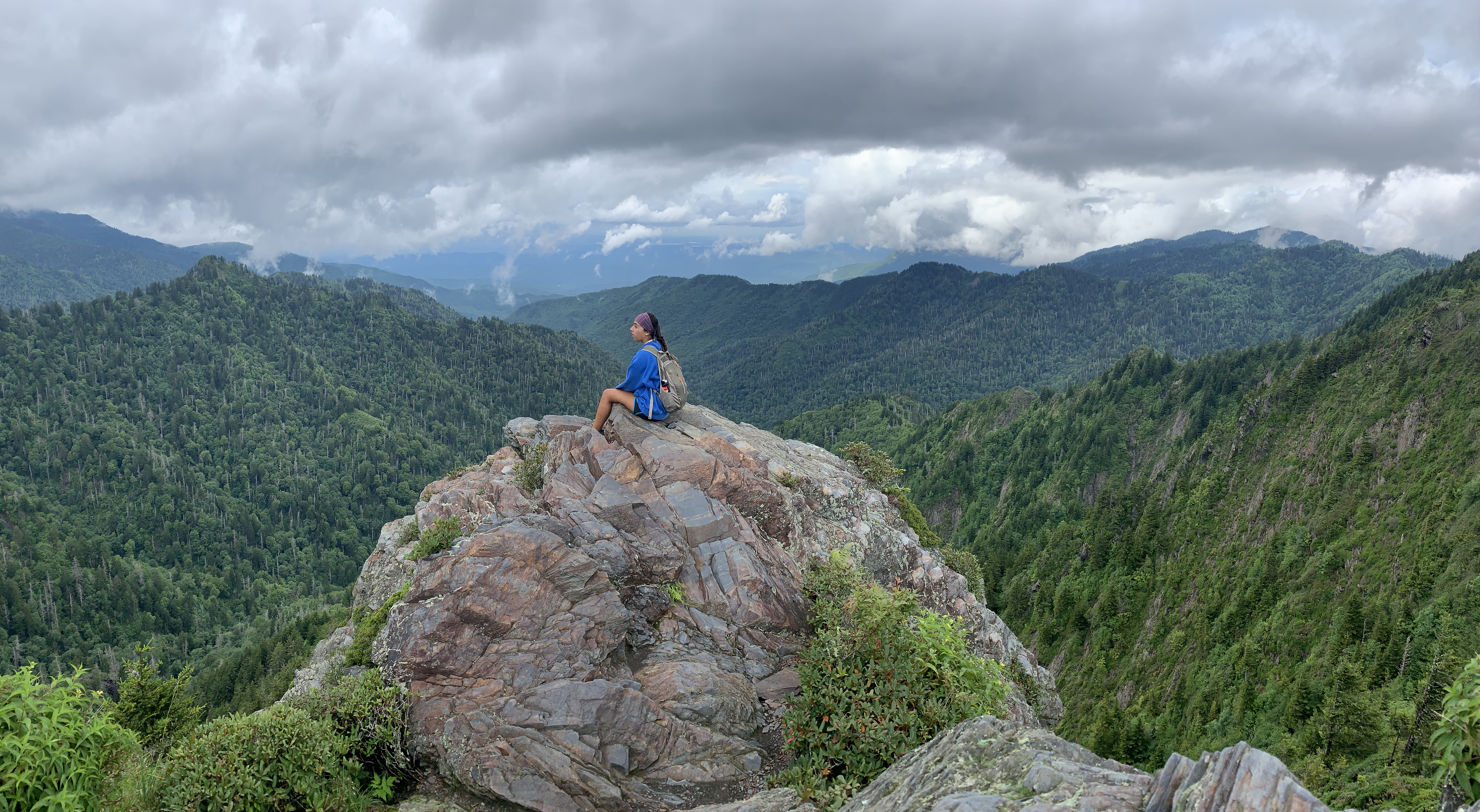 a girl on a boulder in the mountains