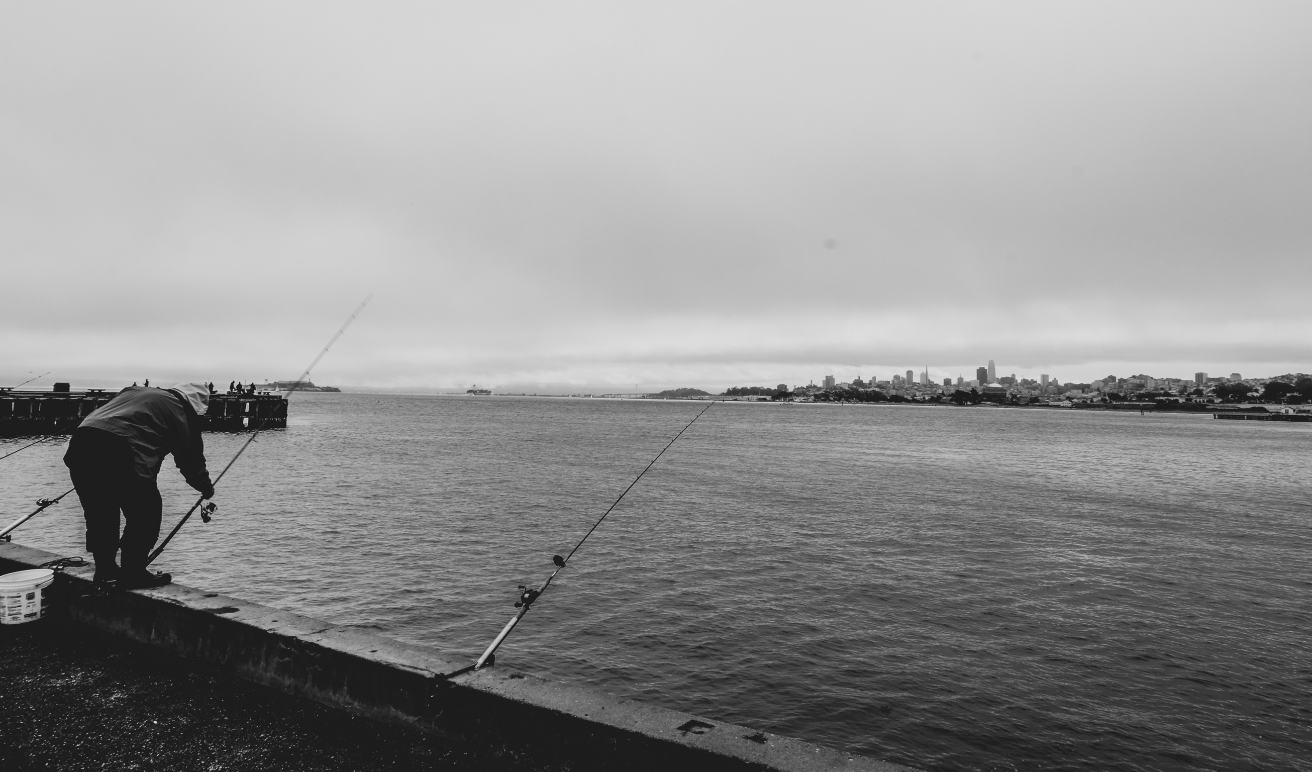 a man sets fishing poles on a pier during a dark cloudy day