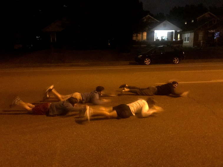 four young men laying down swimming in the street