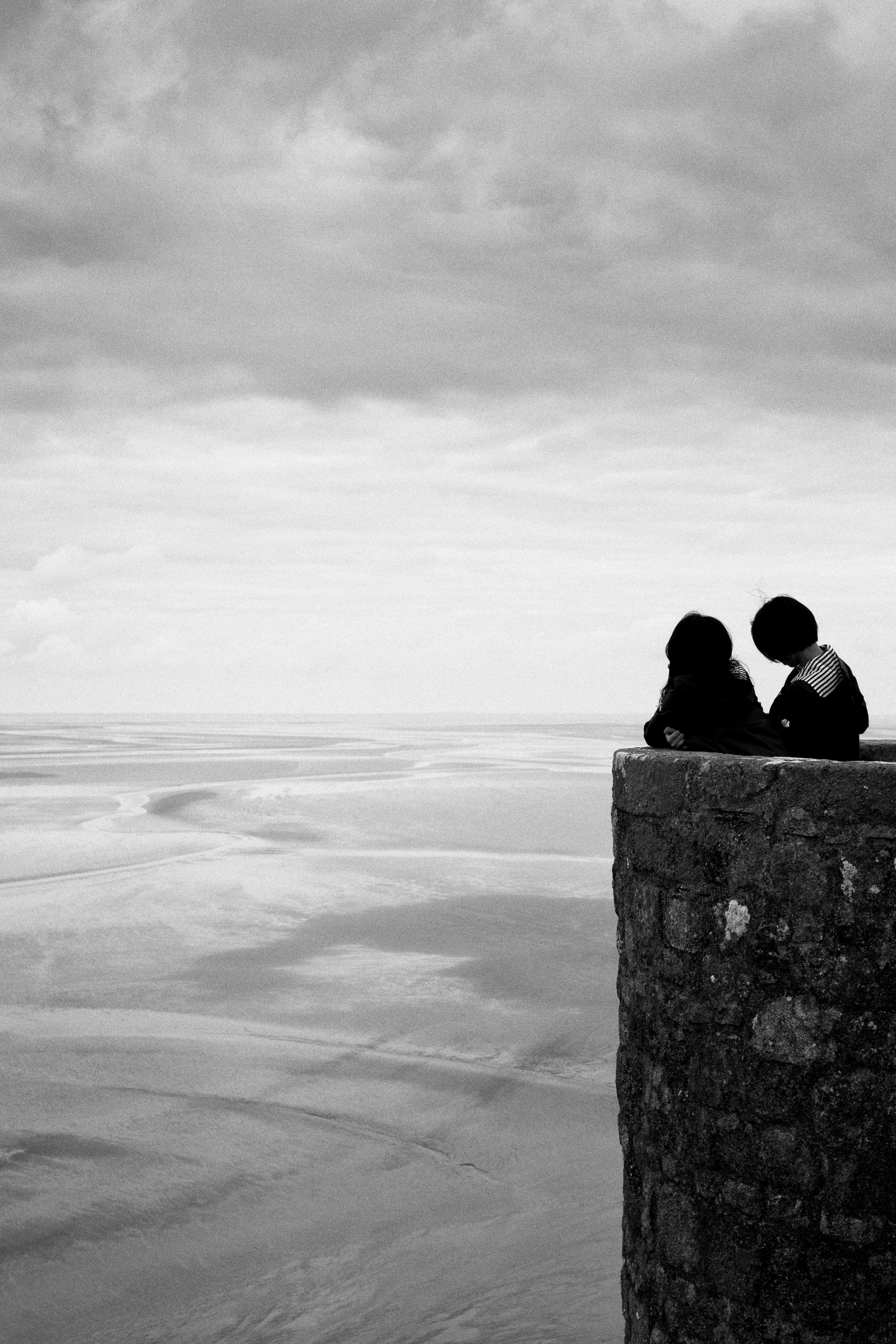 two people look out over a high parapet