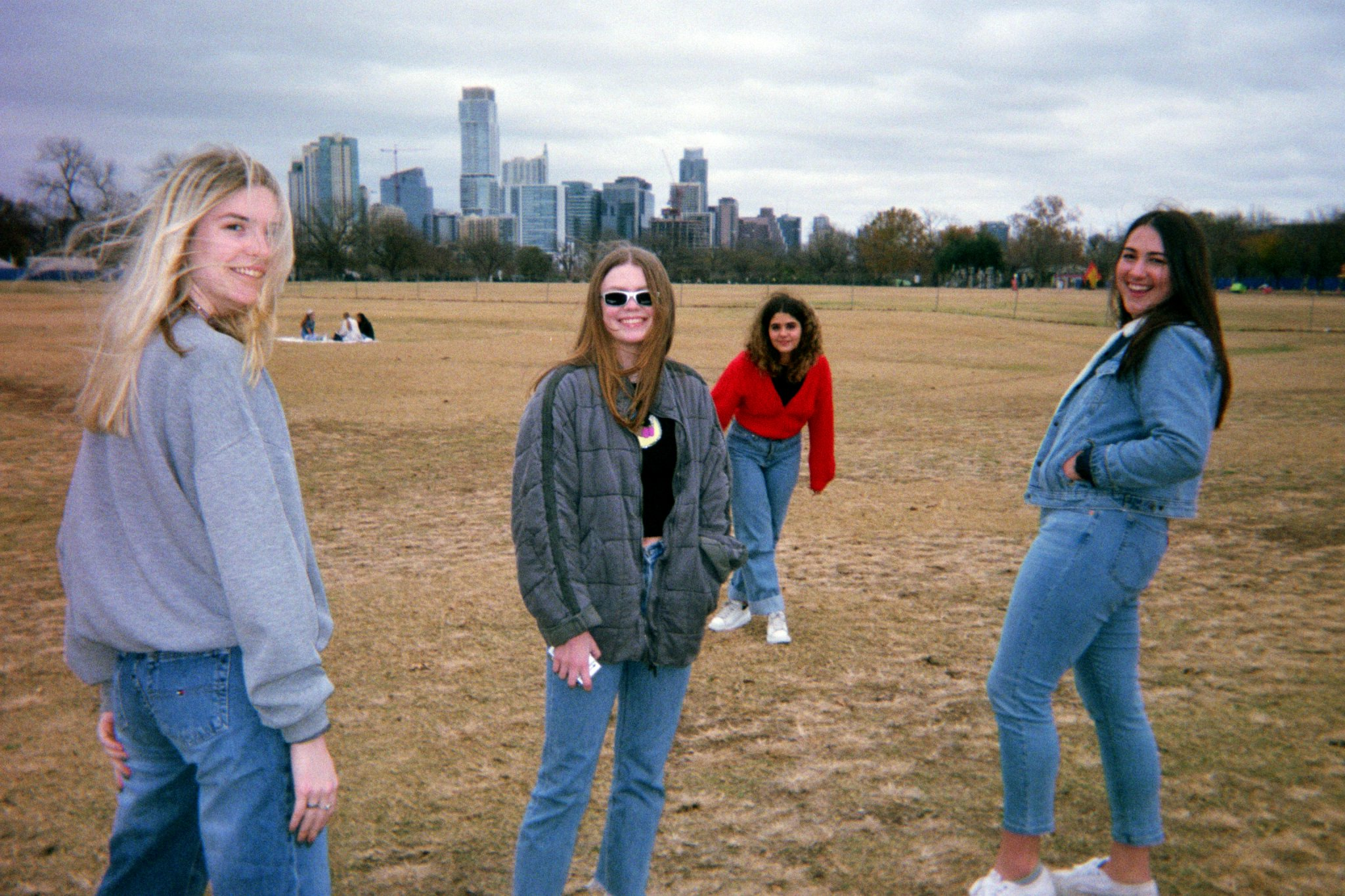 a group of girls in a field with skyscrapers in the background