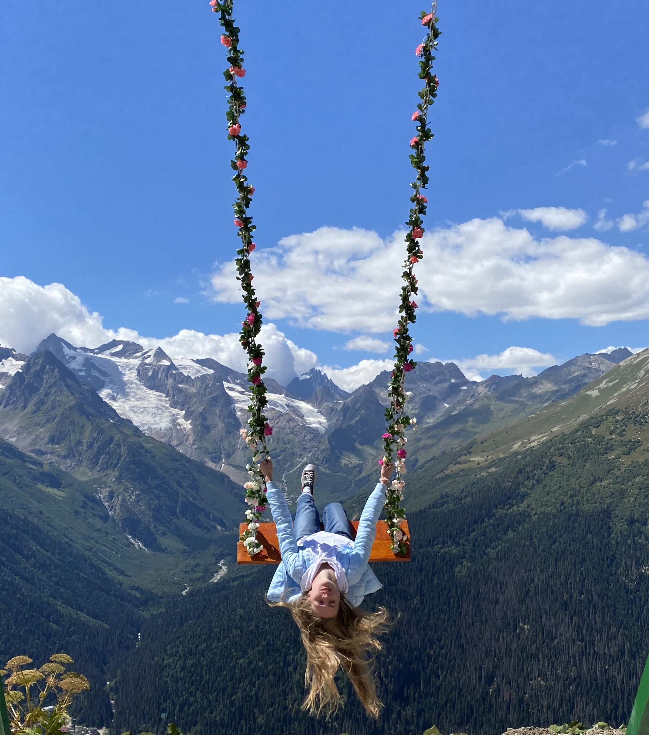 a girl on a swing seems suspended over a valley