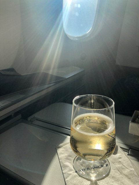a champagne glass catches the sunlight through an airplane window