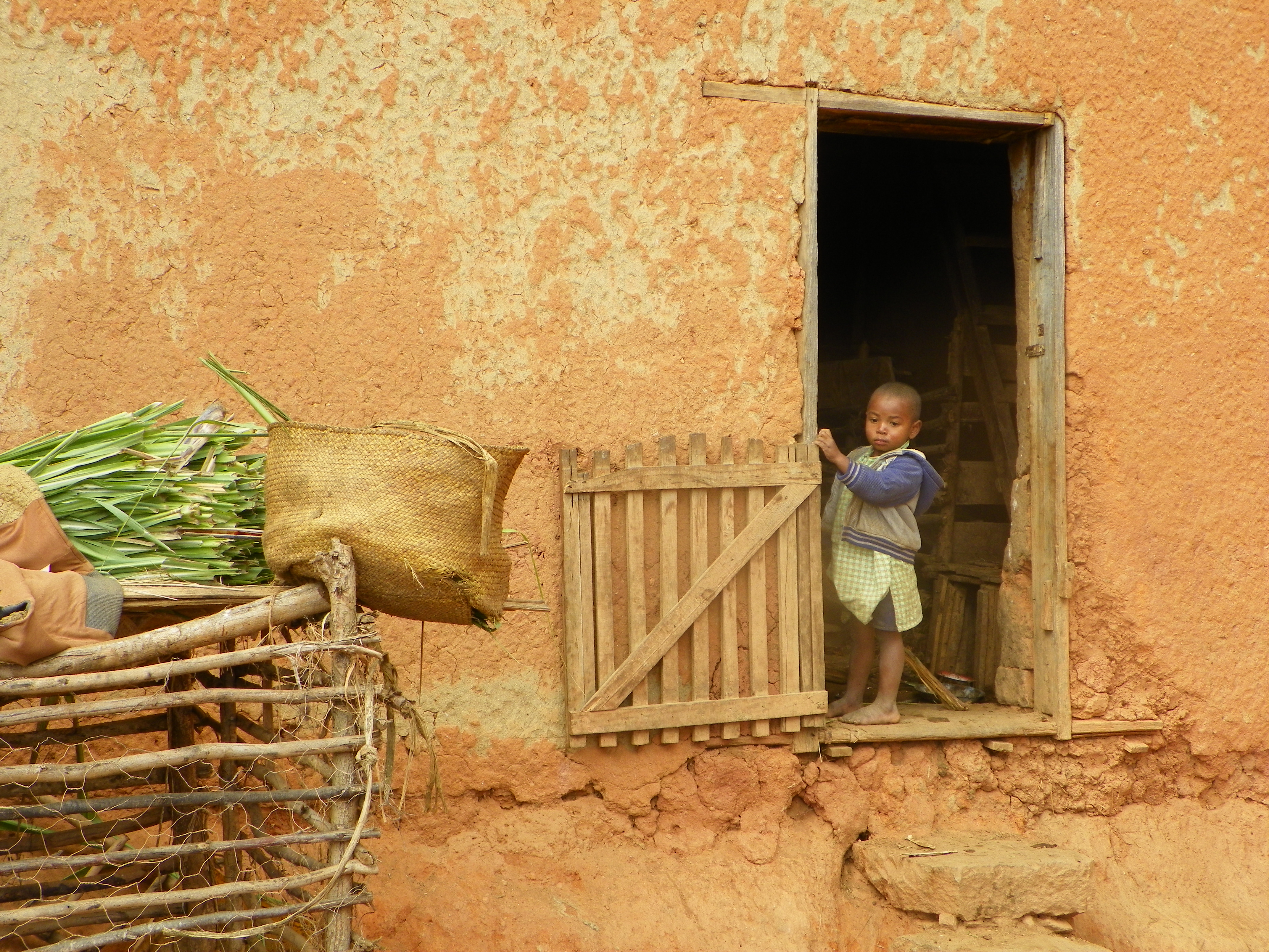 a small child looks out a doorway of an old building