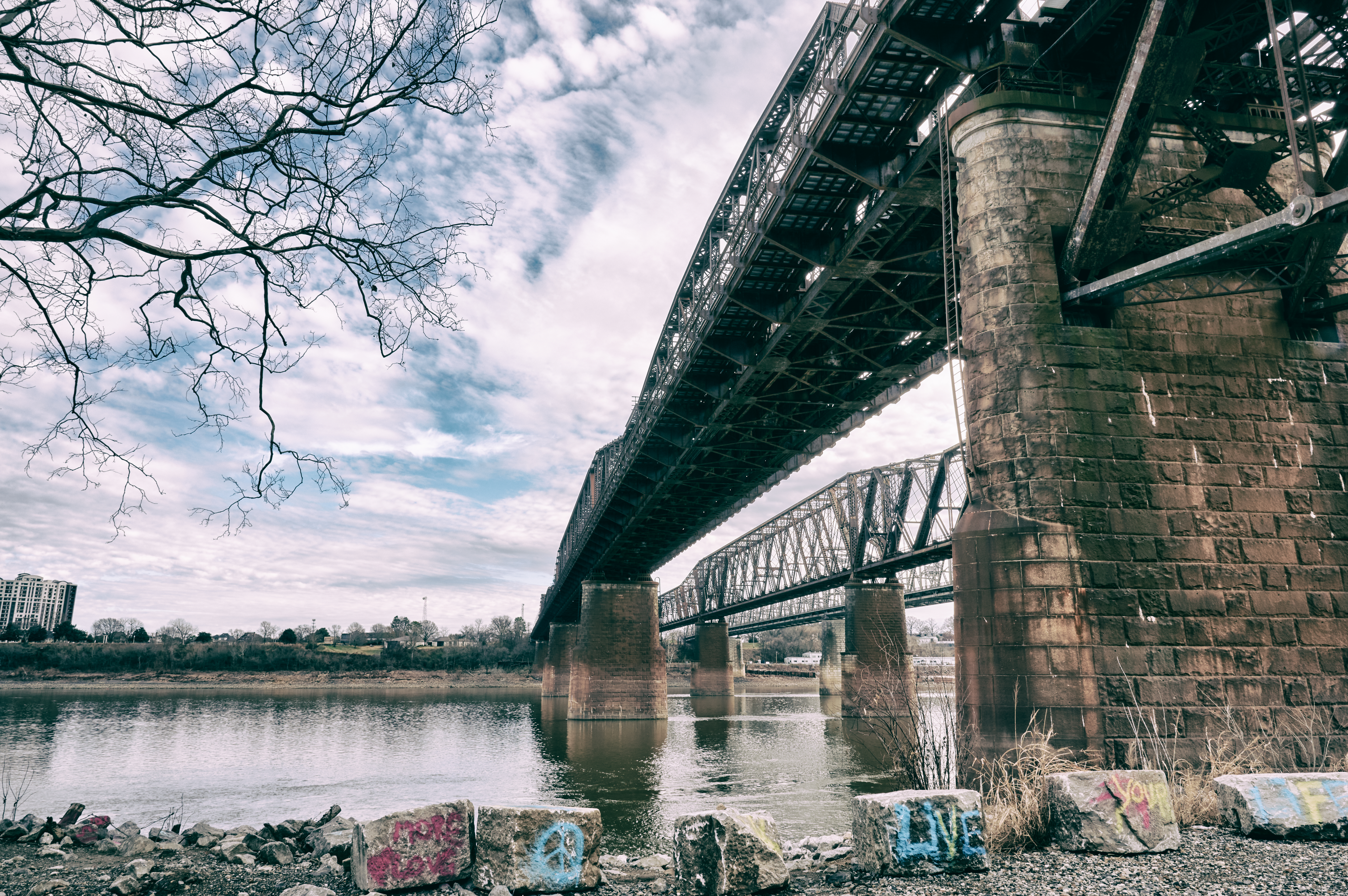 a bridge over a large river with graffiti under it